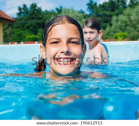 Cute happy girl playing in swimming pool - stock photo