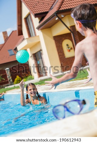 Cute happy girl playing with boy in swimming pool - stock photo