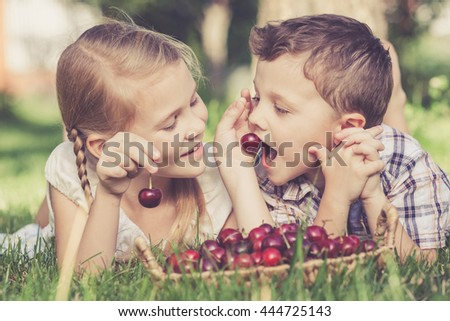 Cute happy little children with basket of cherries lying near the tree in the garden  at the day time. Concept of healthy food. - stock photo