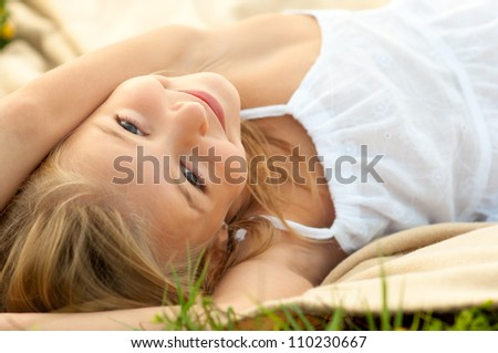 Cute happy little girl in white dress lying on the blanket on beautiful summer day. - stock photo
