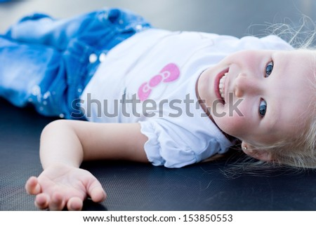Cute happy little girl playing on a trampoline lying on her back grinning at the camera - stock photo