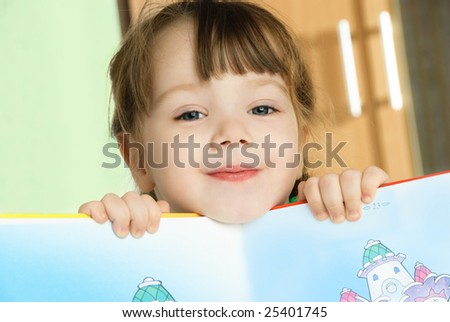cute happy little girl reading a book at home - stock photo