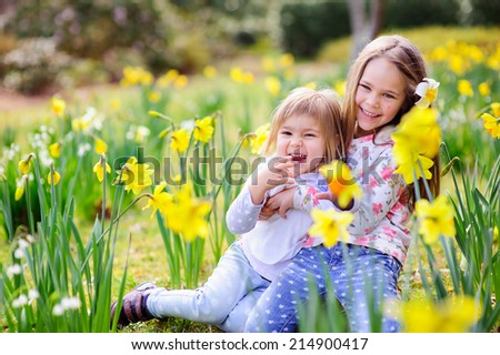 Cute happy little sisters cuddling and having fun in spring meadow - stock photo