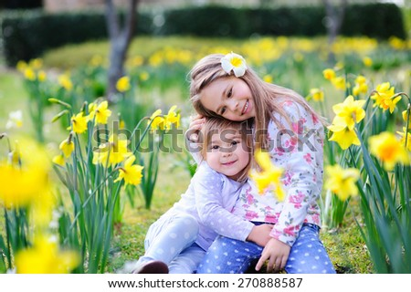 Cute happy little sisters hugging and having fun in spring meadow - stock photo