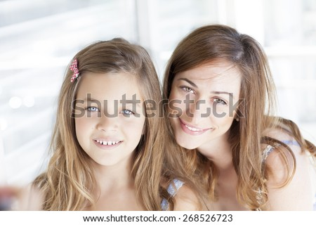 Cute happy mother and daughter looking at camera  - stock photo