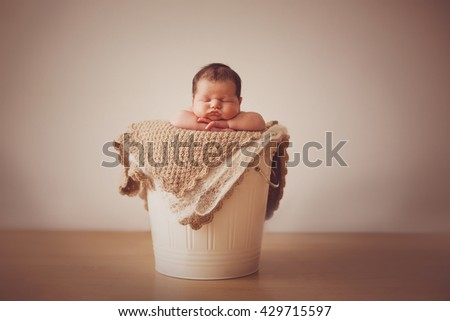 Cute happy newborn baby in a blue knit cap sleeping in a basket - stock photo