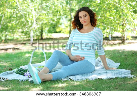 Cute happy pregnant woman on white blanket in the park - stock photo