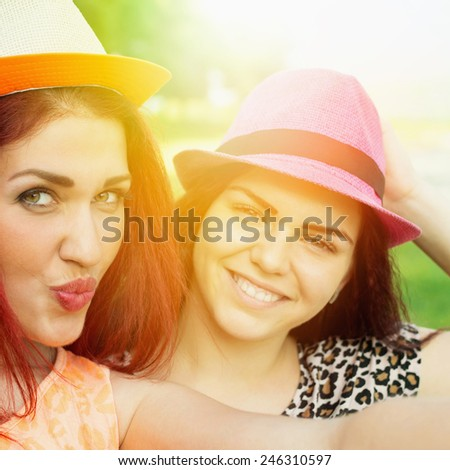 Cute happy redhead teenage girlfriends with pink and orange hats taking a selfie outdoors in park on sunny summer day. Square format, filter, saturated colors. - stock photo