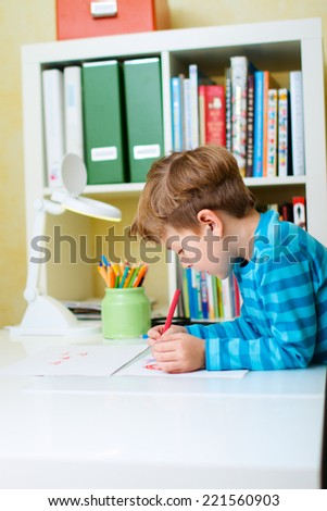 Cute happy schoolkid at home drawing or studying - stock photo