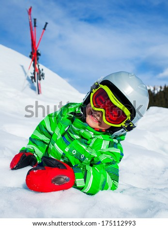 Cute happy skier boy in a winter ski resort. Boy lying in snow. - stock photo