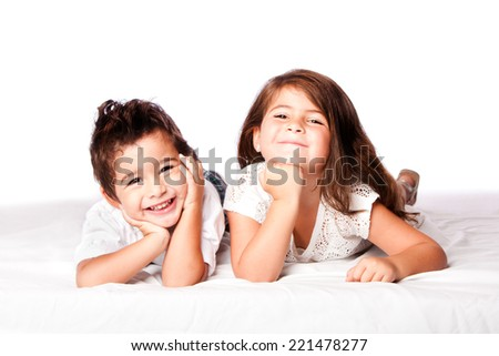 Cute happy smiling brother sister sibling family laying next to eachother, on white. - stock photo