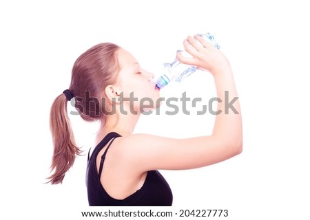 Cute happy teen girl drinking water from bottle after exercises - stock photo