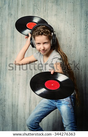 Cute happy teen girl enjoys the music in headphones. Generation. Studio shot. - stock photo