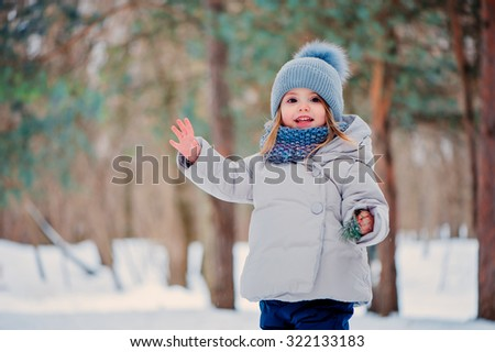 cute happy toddler girl in grey coat and knitted blue scarf and hat having fun on the winter walk - stock photo