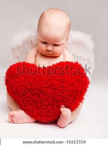 Cute happy valentine angel playing with red heart - stock photo