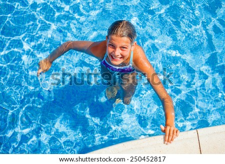 Cute happy young girl swimming and snorking in the swimming pool - stock photo