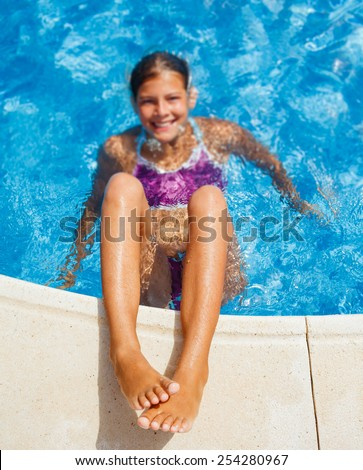Cute happy young girl swimming and snorking in the swimming pool. Focus on the legs, - stock photo