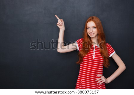 Cute happy young woman with long red hair pointing on copyspace over chalkboard background - stock photo