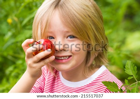 Cute, healthy child holding apple in vegetable garden - stock photo