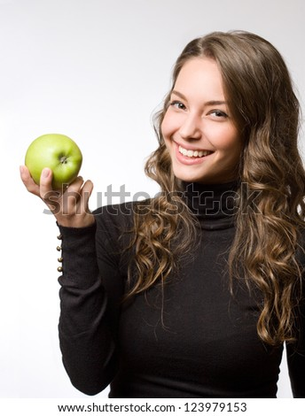 Cute healthy smiling young brunette holding fresh green apple. - stock photo
