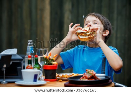 Cute healthy teenager boy eats hamburger and potato sitting in cafe outdoors - stock photo