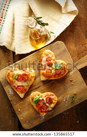 Cute heart shaped mini pizzas topped with cheese and tomato and garnished with fresh basil served on an old wooden board in the kitchen with virgin olive oil - stock photo