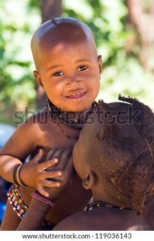 Cute Himba boy plays with his brother - stock photo