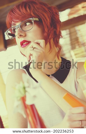 Cute hipster teenage girl in a coffee shop, daydreaming, looking away. Retro styled, toned image  - stock photo