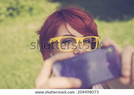Cute hipster teenage girl taking a photo with her purple smart phone, retro colors - stock photo