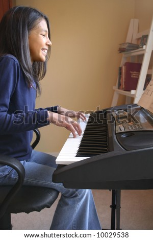 Cute hispanic girl playing piano - stock photo