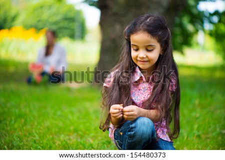Cute hispanic girl take seat in park with mother on background - stock photo