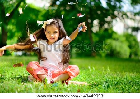 Cute hispanic girl throwing confetti at park - stock photo