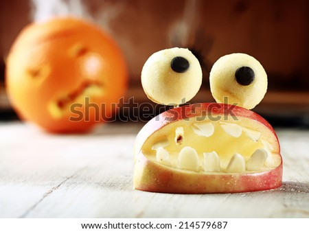 Cute homemade Halloween apple decoration of an open mouth with teeth topped with googly dough eyes on toothpicks for a scary but healthy favor to give children trick-or-treating - stock photo