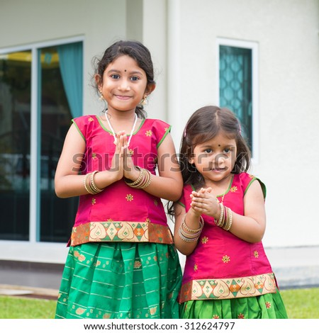 Cute Indian girls dressed in sari with folded hands representing traditional Indian greeting, standing outside their new house celebrating diwali, festival of lights. - stock photo
