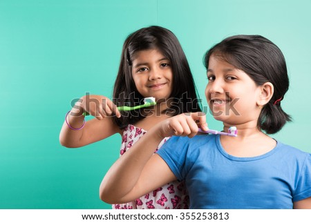cute indian girls posing with tooth brush, indian girls and brushing, asian girls with tooth brush & paste, indian girls caring their teeth, indian girls & oral care, indian girls & bed time brushing - stock photo