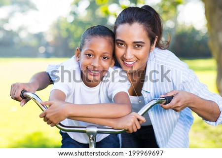 cute indian mother and her daughter outdoors in park on a bike - stock photo