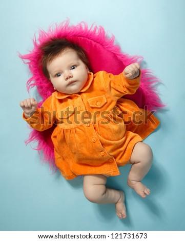 cute infant baby girl in orange dress, beautiful kid's full length portrait, studio shot - stock photo