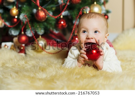 cute infant boy plays with Christmas ball on the fur  - stock photo