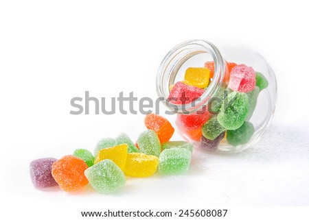 Cute jar full of assorted colorful candies with white background. Image has grain or blurry or noise and soft focus when view at full resolution. (Shallow DOF, slight motion blur) - stock photo