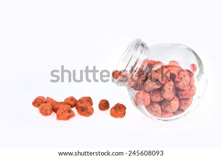 Cute jar full of assorted preserved Red Plum with white background. Image has grain or blurry or noise and soft focus when view at full resolution. (Shallow DOF, slight motion blur) - stock photo