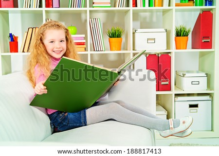 Cute joyful girl sitting on a sofa with a huge book. Home. - stock photo