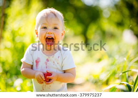 Cute joyous child with strawberry - outdoor in backyard garden on sunny day - stock photo