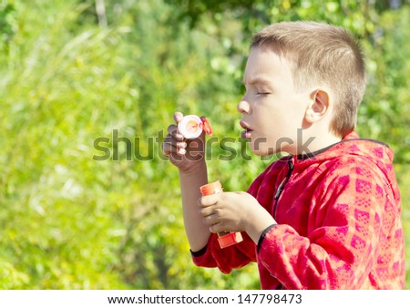 Cute kid blowing bubbles outdoors, in the forest in a beautiful sunny afternoon  - stock photo