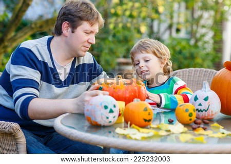 Cute kid boy and his father making jack-o-lantern for halloween in autumn garden, outdoors. Family having fun together - stock photo