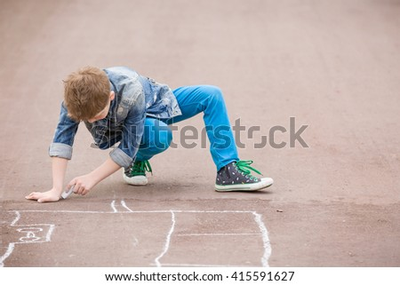 Cute kid boy drawing with chalk on the pavement in the park. Summer activities for children. Creative child drawing with blue chalk on the road. - stock photo