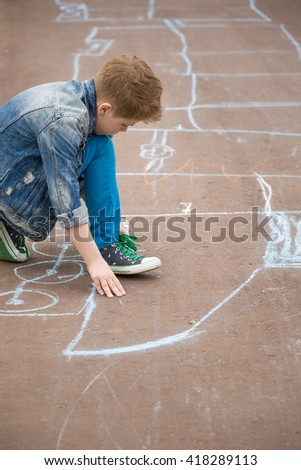 Cute kid boy drawing with chalk on the pavement in the park. Summer activities for children outdoors. Creative child drawing with blue chalk on the road. Learning and activities - stock photo