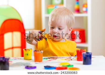 cute kid boy painting at home or playschool - stock photo