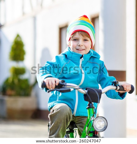 Cute kid boy riding with his first green bike in the city. Happy child in colorful clothes. Active leisure for kids outdoors. - stock photo