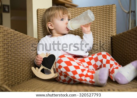 Cute kid girl at home drinking milk - stock photo