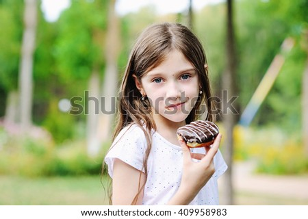 Cute kid girl eating sweet donut outdoor in the park on sunny warm day - stock photo